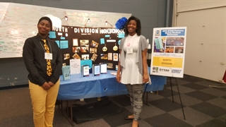 North Division students Qiaira Matthews (left) and Tatiana Loyd (right) showcase their mobile app -- which is now one of six winners in a national competition -- at the MPS STEM Partners Spring Student Showcase
