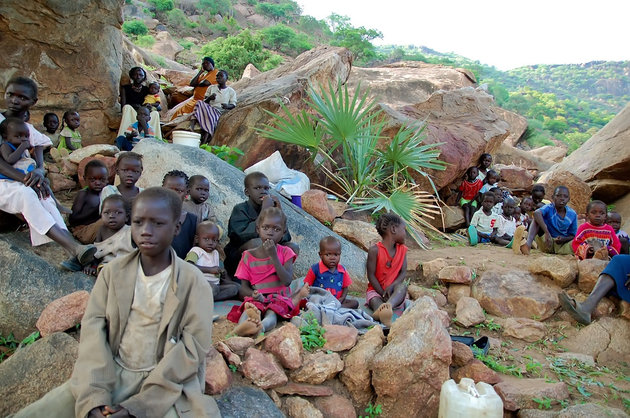 During the day women and children climb rocky hillsides near Kauda in central Sudan's Nuba Mountains to seek cover from government air strikes. At night they climb back down from the shelter. (Alan Boswell/MCT via Getty Images)