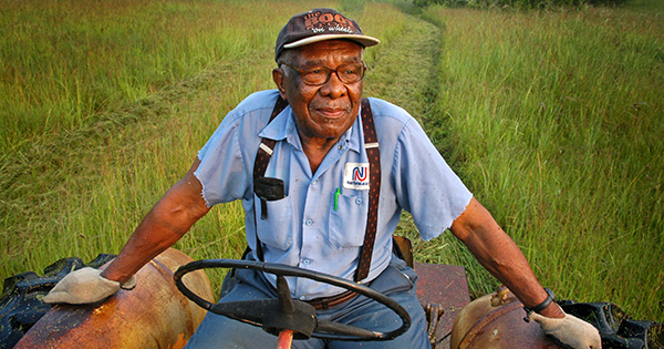 "Eddie Cotton, 82, Hermanville, MS,  clears a field for a fall crop of hay, using a 40-yr-old tractor. He is among thousands of black farmers denied federal loans in past years. ""They took away my ability to provide  for my family,"" he says of the discrimination.©Robin Nelson/ZUMA"