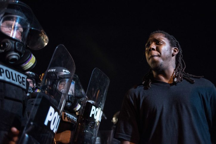 CHARLOTTE, NC - SEPTEMBER 21: Police officers face off with protestors  on the I-85 (Interstate 85) during protests following the death of a man shot by a police officer on September 21, 2016 in Charlotte, NC. The protests began the previous night following the fatal shooting of 43-year-old Keith Lamont Scott at an apartment complex near UNC Charlotte. (Photo by Sean Rayford/Getty Images)