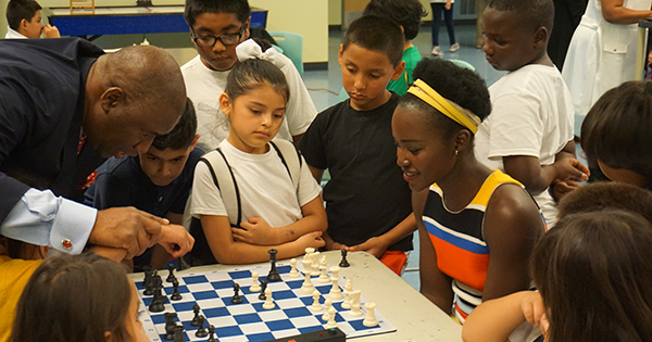Orrin Hudson, founder of Be Someone, and actress Lupita Nyong'o teaching the game of chess to a group of young children during a promotional event for the film.