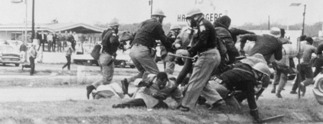 (Original Caption) Selma, Alabama: End Of The March. SNCC leader John Lewis (light coat, center), attempts to ward off the blow as a burly state trooper swings his club at Lewis' head during the attempted march from Selma to Montgomery March 7th. Lewis was later admitted to a local hospital with a possible skull fracture.
