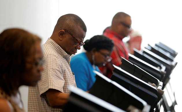 A voter casts his ballot during early voting at the Beatties Ford Library in Charlotte, North Carolina October 20, 2016. REUTERS/Chris Keane