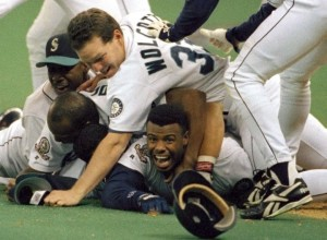 FILE - In this Oct. 8, 1995, file photo, Seattle Mariners' Ken Griffey Jr. smiles from beneath a pile of teammates who mobbed him after he scored the winning run in the bottom of the 11th inning of a baseball game against the New York Yankees in Seattle. The transcendent, once-in-a-generation athlete belonged to a little pocket of the country that never had the experience of the best athlete in their respective sport be theirs. And it's why when Griffey is all but certain to be announced as a Baseball Hall of Fame inductee next week, he'll take the entire Northwest with him to Cooperstown.  (AP Photo/Elaine Thompson, File) NY164