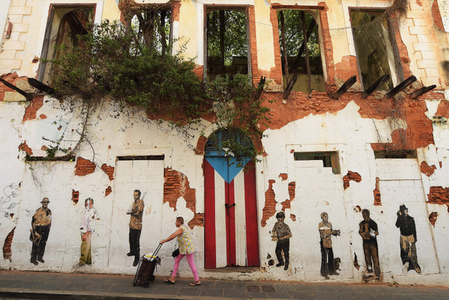 OLD SAN JUAN, PUERTO RICO - JULY 04: A woman walks by a rundown building on Saturday July 04, 2015 in Old San Juan, Puerto Rico. The historic area brings in many tourists. (Photo by Matt McClain/ The Washington Post via Getty Images)