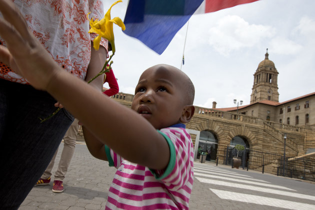 A father and his son holding a South African flag prepare to lay flowers at a makeshift memorial at the Union Buildings in Pretoria, South Africa, Saturday Dec. 7, 2013, where preparations are underway for Nelson Mandela to lie in state for three days prior to burial in his hometown of Qunu. South Africa is readying itself for the arrival of a flood of world leaders for the memorial service and funeral of Nelson Mandela as thousands of mourners continued to flock to sites around the country Saturday to pay homage to the freedom struggle icon. (AP Photo/Peter Dejong)