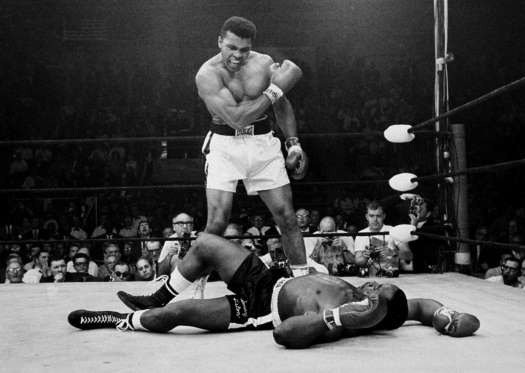 Ali stands over fallen challenger Sonny Liston, shouting and gesturing shortly after dropping Liston with a short hard right to the jaw on May 25, 1965, in Lewiston, Maine. The bout lasted only one minute.