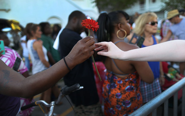 CHARLESTON, SC - JUNE 20:  A flower is handed out as people with the Black Lives Matter movement pass the Emanuel African Methodist Episcopal Church during a walk to commemorate the lives lost in the shooting on June 20, 2015 in Charleston, South Carolina. Dylann Roof, 21 years old, has been charged with killing nine people during a prayer meeting in the church on June 17.  (Photo by Joe Raedle/Getty Images)