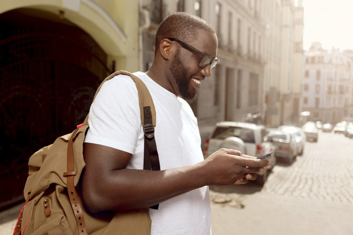 Pleasant smiling man using cellphone