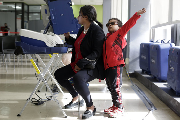 A young boy stretches as he stands next to a woman filling out her ballot during early voting at a polling station inside Truman College on October 31, 2016 in Chicago, Illinois. / AFP / Joshua Lott        (Photo credit should read JOSHUA LOTT/AFP/Getty Images)